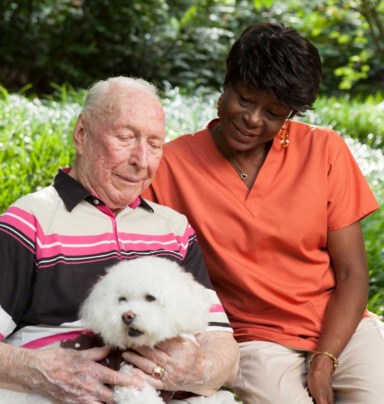 Caregiver with Canterbury Court resident holding his dog