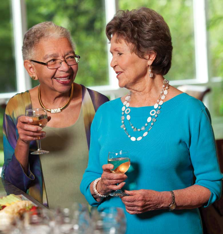 Senior women talking together while enjoying a glass of wine
