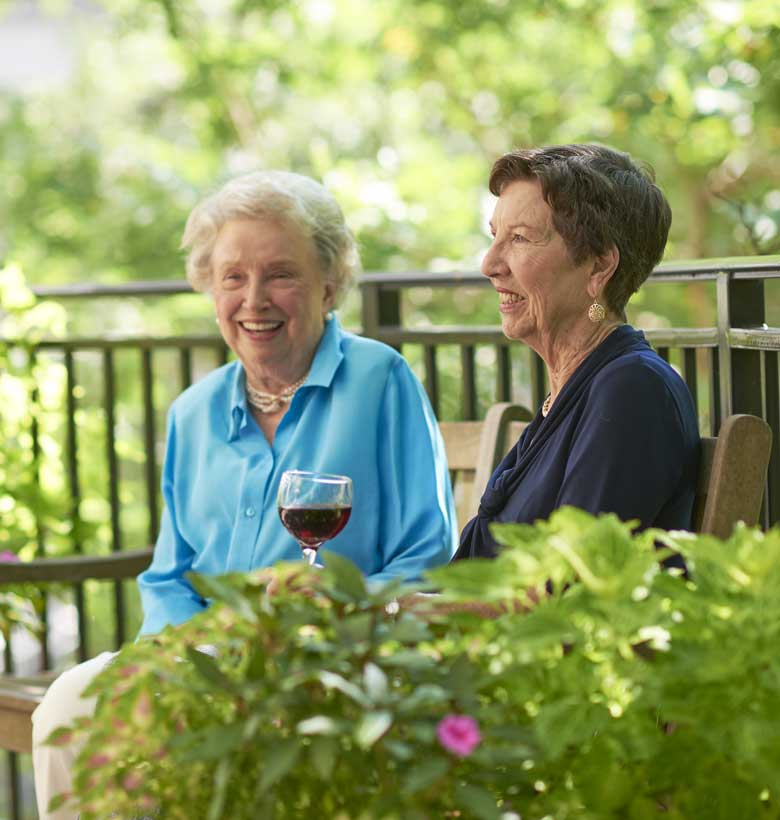 Senior women drinking and talking on bench at Canterbury Court