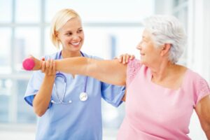 A senior woman and her doctor work on occupational therapy for seniors.