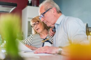 A senior man and woman reviewing finances for retirement living.