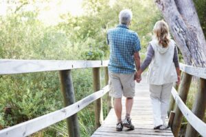 Two seniors with good mobility walking on a wooden bridge.