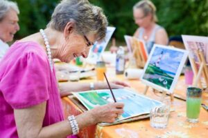 Seniors painting together outdoors