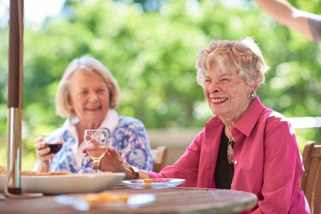 seniors enjoying wine outside on a patio