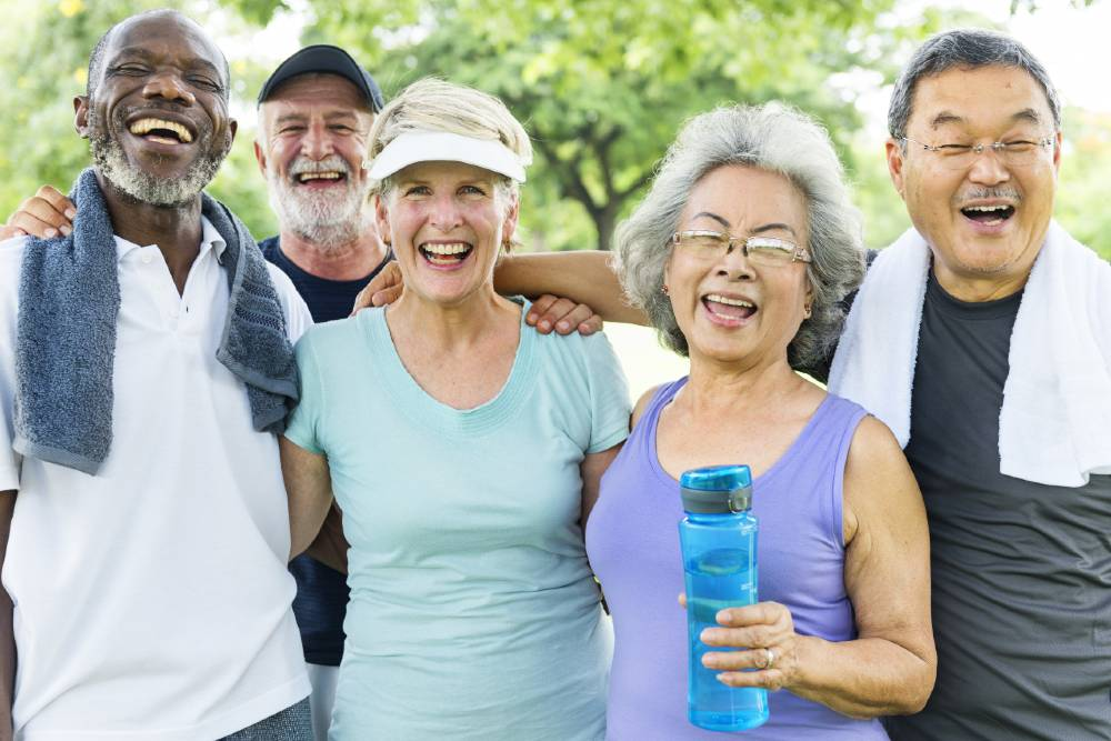 Group of seniors outside laughing and exercising