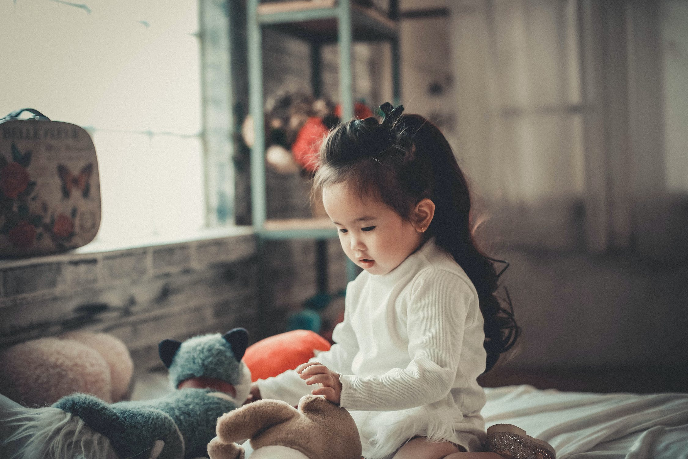 Girl at home with stuffed toys