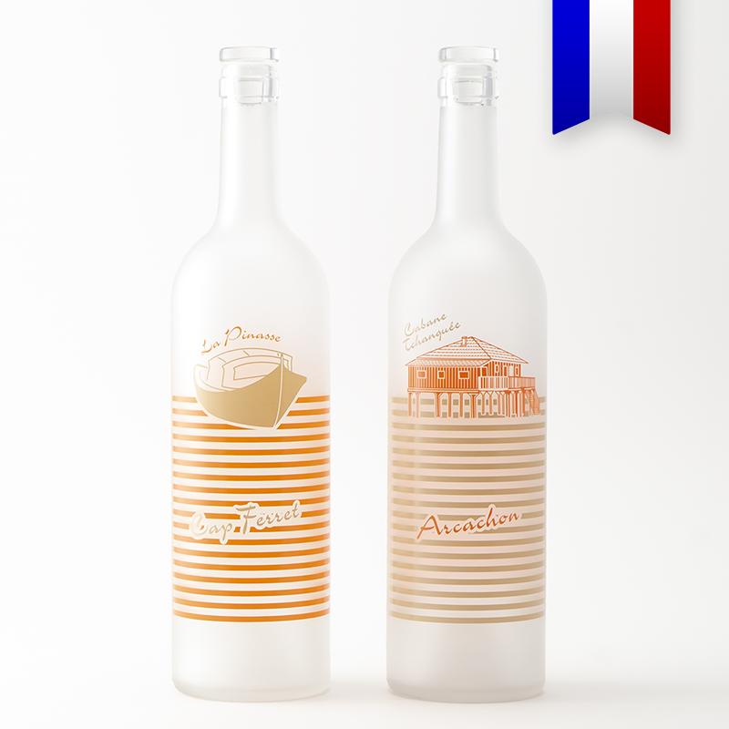 Les bouteilles personnalisées «Pinasse tchanqué» icône du bassin d'Arcachon et de la presqu'île du Cap Ferret. La carafe bordelaise satinée au décor orange et beige sera parfaite pour siroter au bord de l'eau!