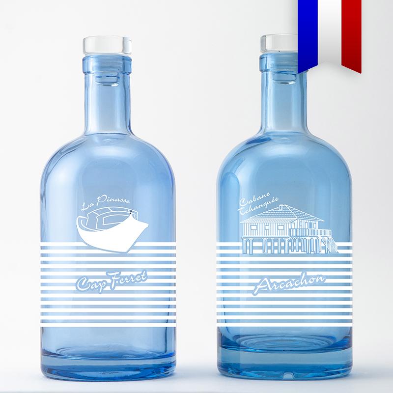 Au fil du temps, les bouteilles personnalisées «Pinasse tchanqué» sont devenues iconiques du bassin d'Arcachon et de la presqu'île du Cap Ferret. La carafe Island bleue décorée en est une des plus belles représentations.