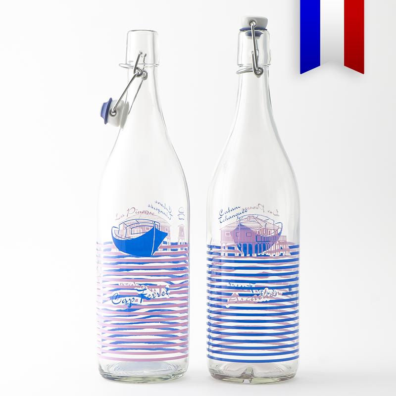 La gourde en verre 1 L personnalisée à bouchage mécanique «Pinasse Tchanqué» au décor bleu et rose est une belle alternative à la bouteille en plastique. Durable et Made in France, c'est une bouteille magnifique à la ville comme à la plage!