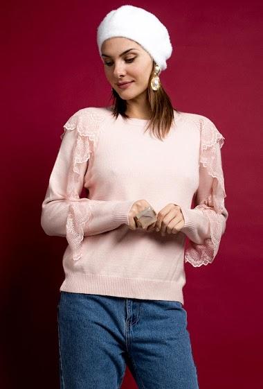 Feminine sweater with ruffles. The model measures 175 cm