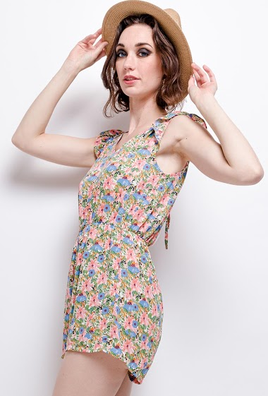 Playsuit with printed flowers, open back with lace. The model measures 177 cm