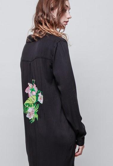 Chemise douce et fluide, fentes latérales, dos avec fleurs brodées, sequins, coupe droite. La mannequin mesure 177 cm et porte du S