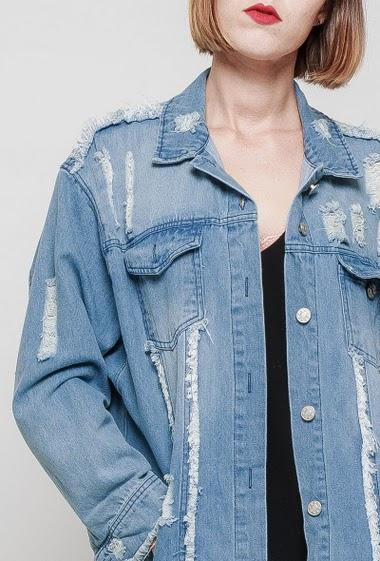 Veste longue en jean usé, détail franges, bords effilochés, coupe droite.  Le mannequin mesure 172 cm et porte du S