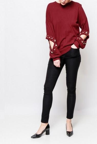 Knitted sweater with cutworked sleeves, decorative pearls. The model measures 170cm, one size corresponds to 38-40
