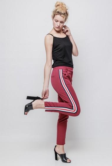 Pantalon chino a bandes laterales blanches. la mannequin mesure 177 cm et porte du S