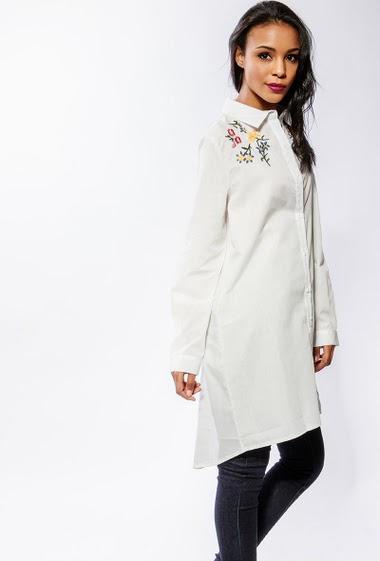 Chemise avec fleurs brodées, coupe longue. La mannequin mesure 170cm et porte du S/M