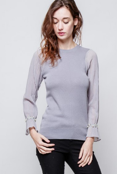 Knitted sweater, transparent long sleeves decorated with pearls. The model measures 177cm, one size corresponds to 38-40
