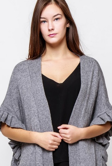Soft knitted poncho, ruffle border. The model measures 172cm