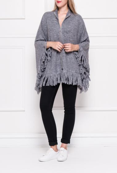 Soft knit poncho decorated with strass on the front, border with fringes