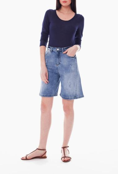 flared shorts in faded jeans and worn