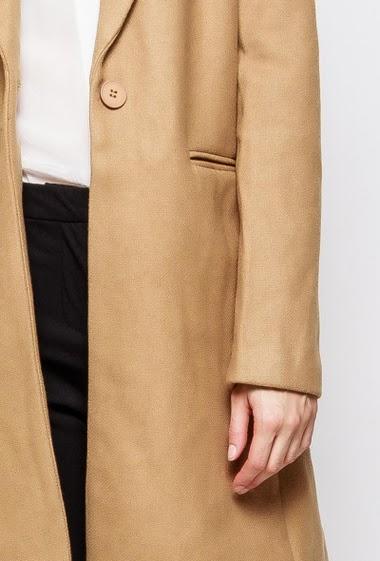 Manteau élégant avec poches. La mannequin mesure 178 cm et porte du M