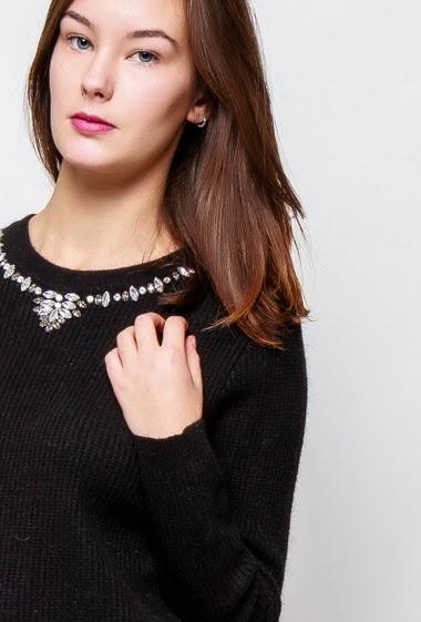 Pull en maille côtelée, dos avec nœud, col orné de perles diamants. La mannequin mesure 172cm et porte du S
