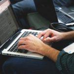 Hombre busca en internet con su ordenador