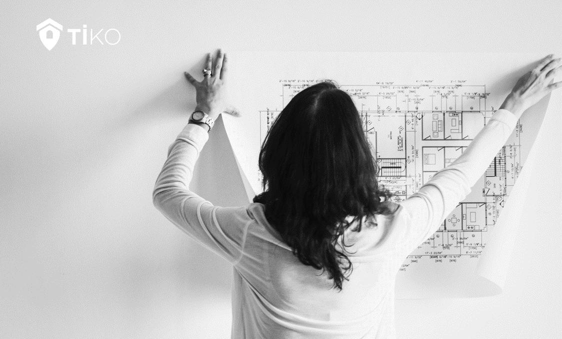 Una mujer sujeta un plano de una vivienda