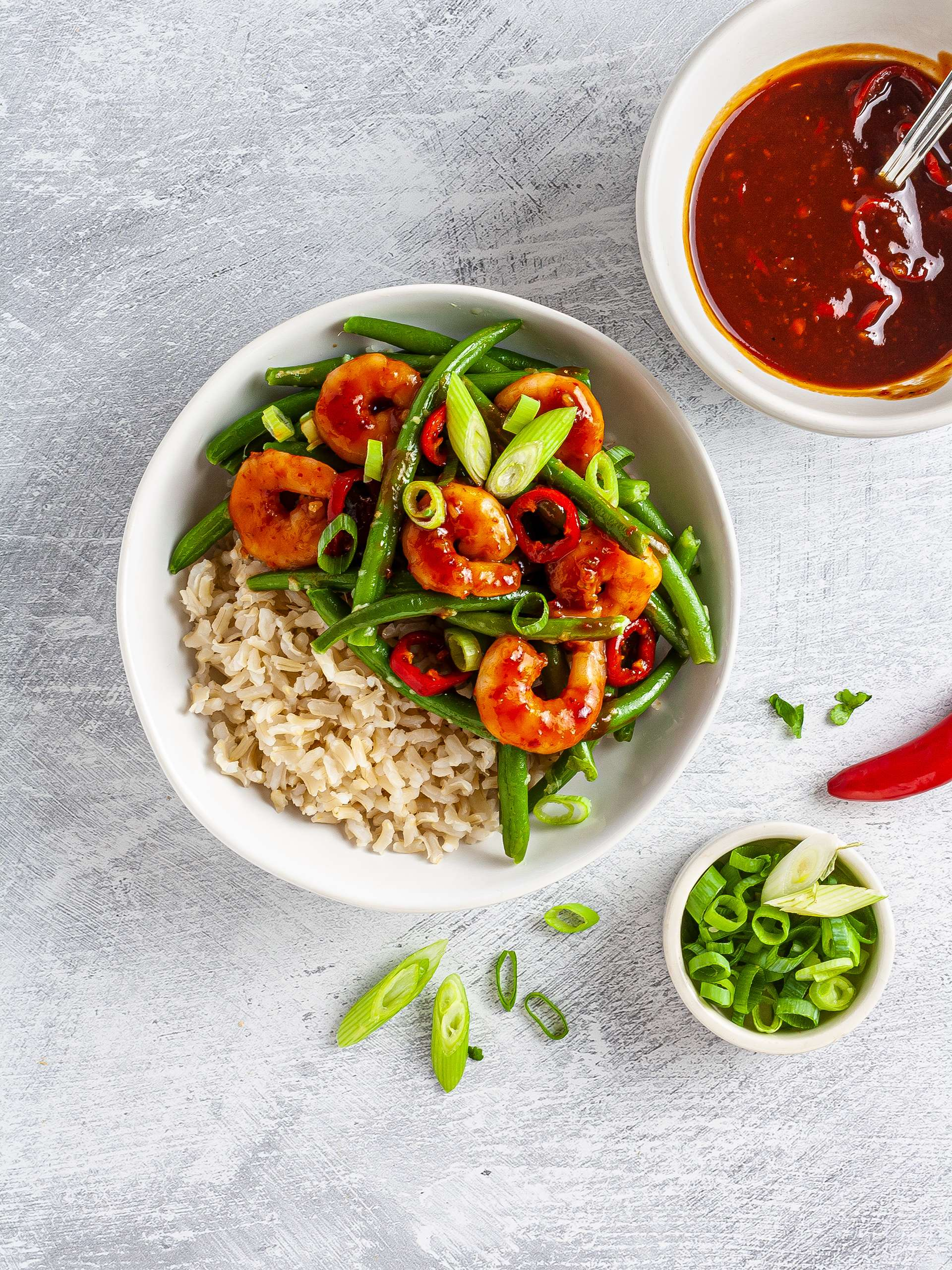 Sweet chili prawns bowl with brown rice, green beans, and spring onions