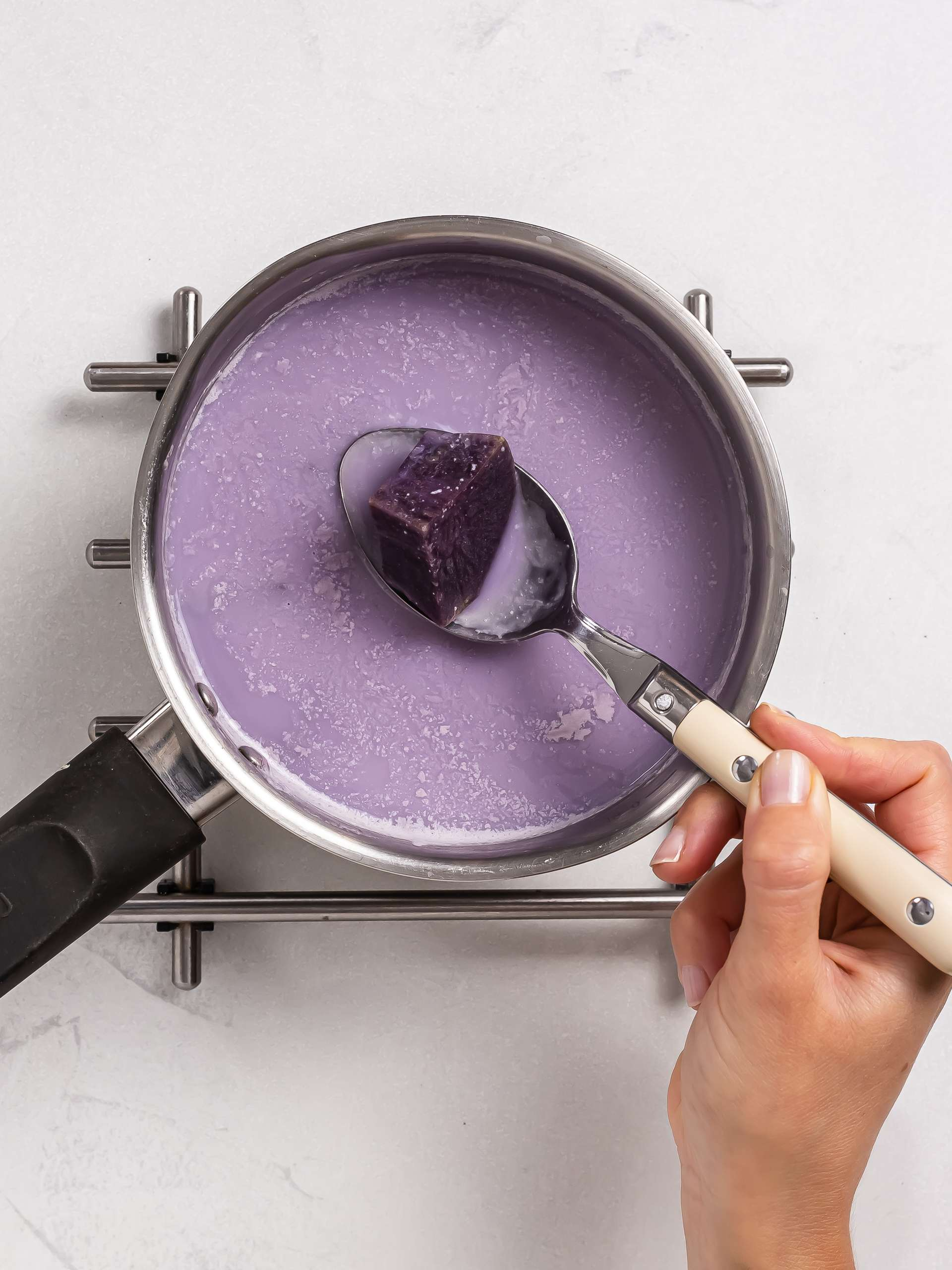 cooking ube with milk in a pot