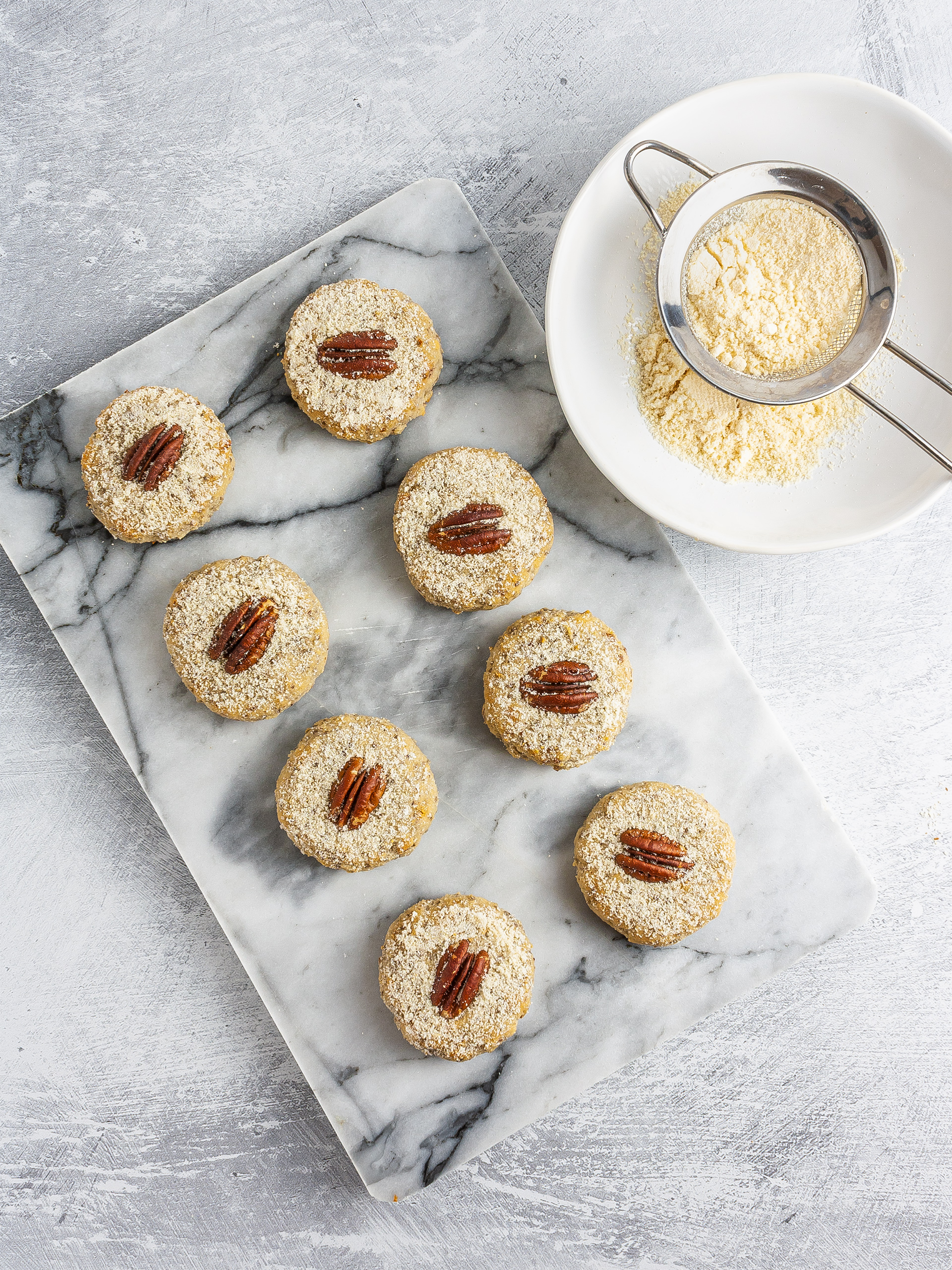 Baked pecan sandies dusted with almond meal