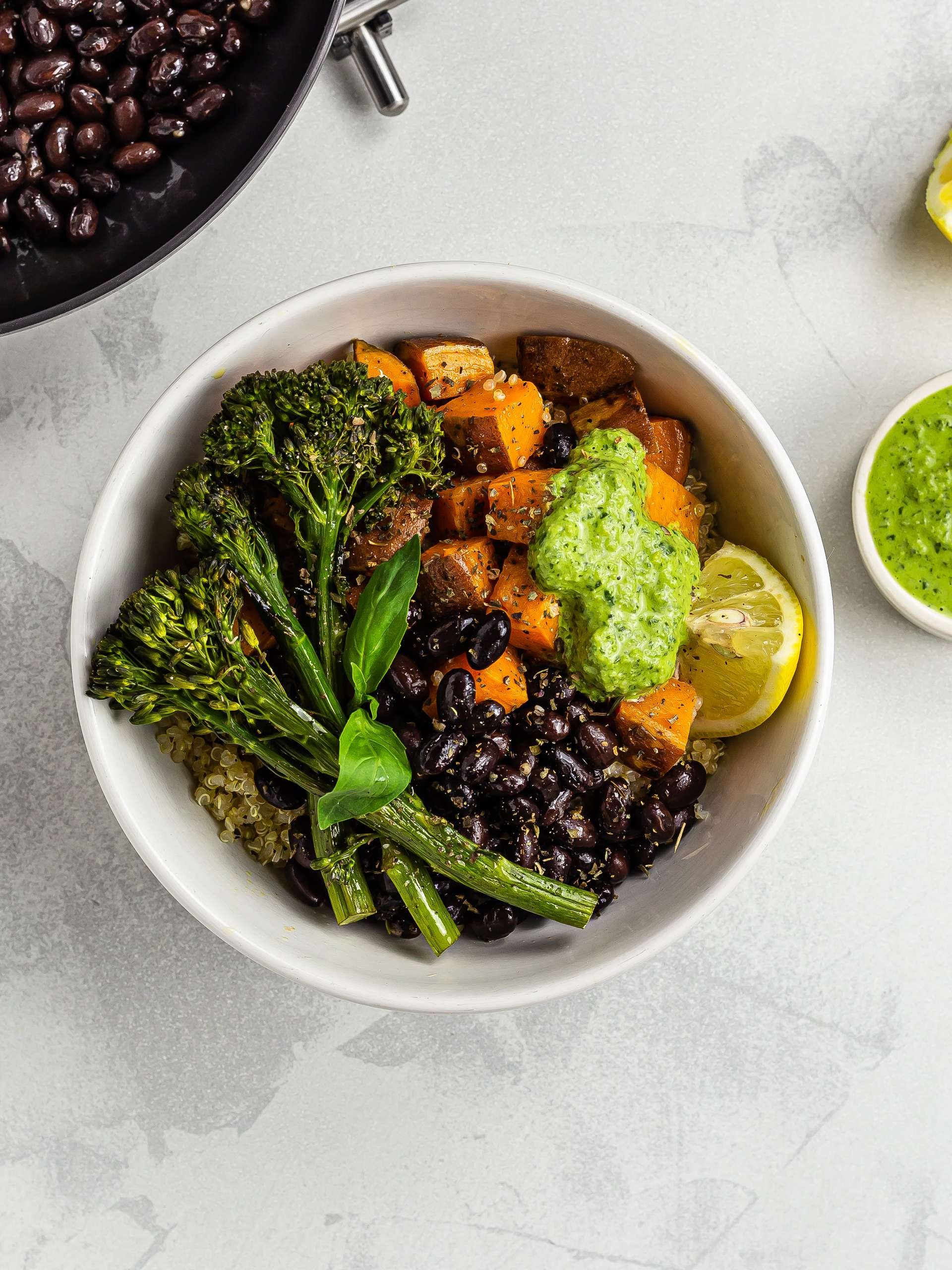 Sweet potato quinoa bowl with black beans and green tahini pesto