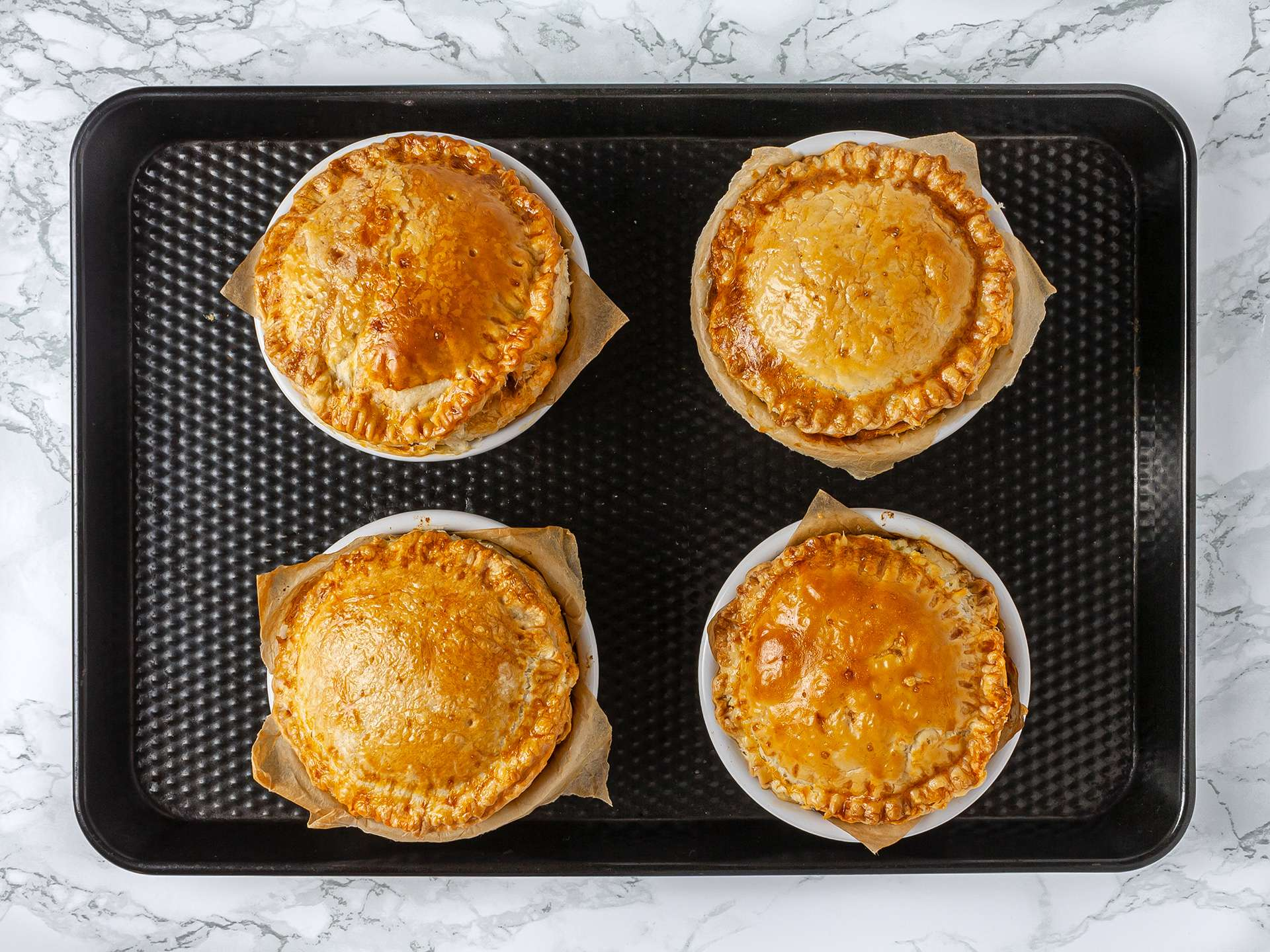 Single portion mince lamb pies baked in the oven on a tray