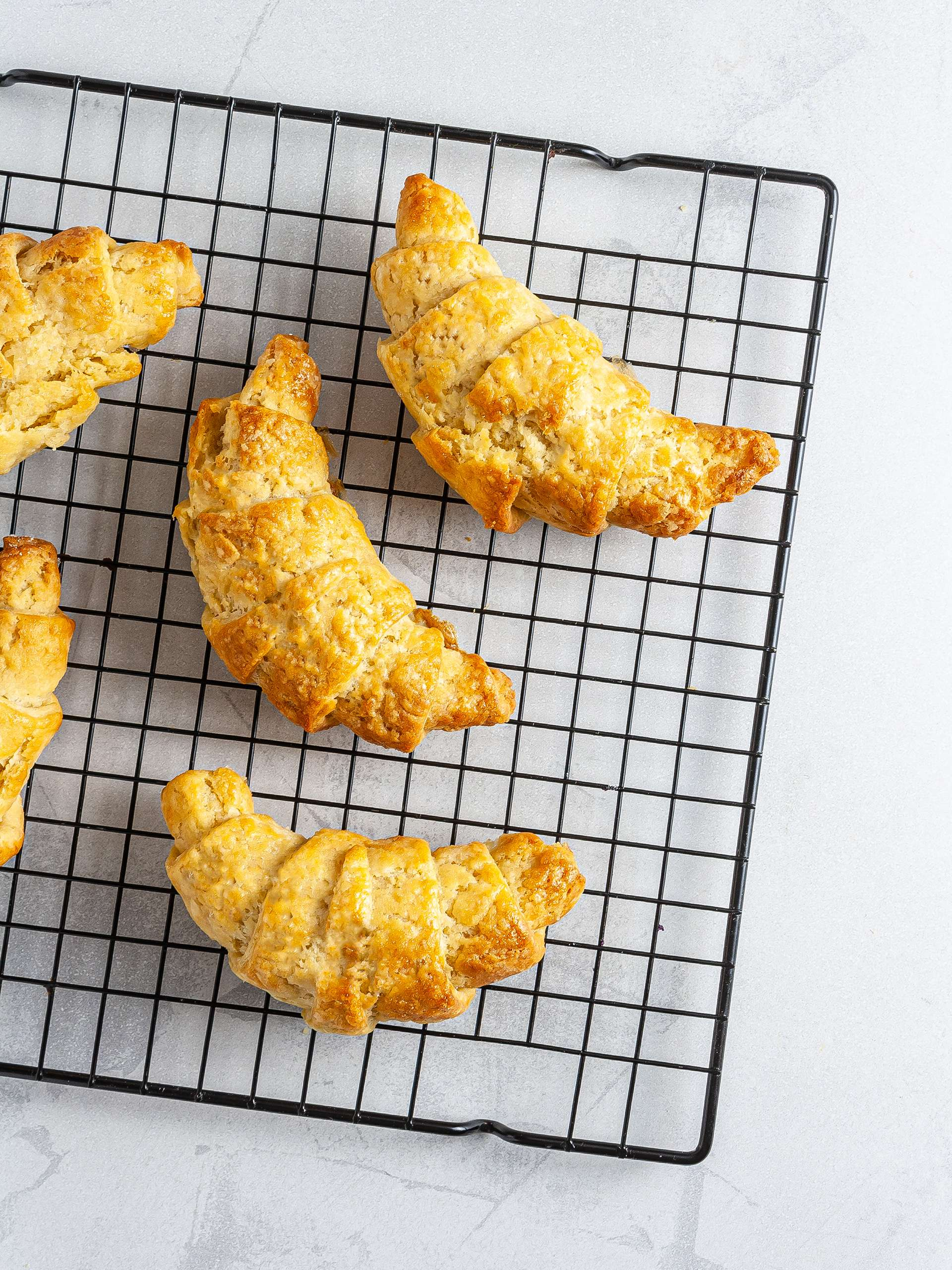 Baked croissants on a wire rack