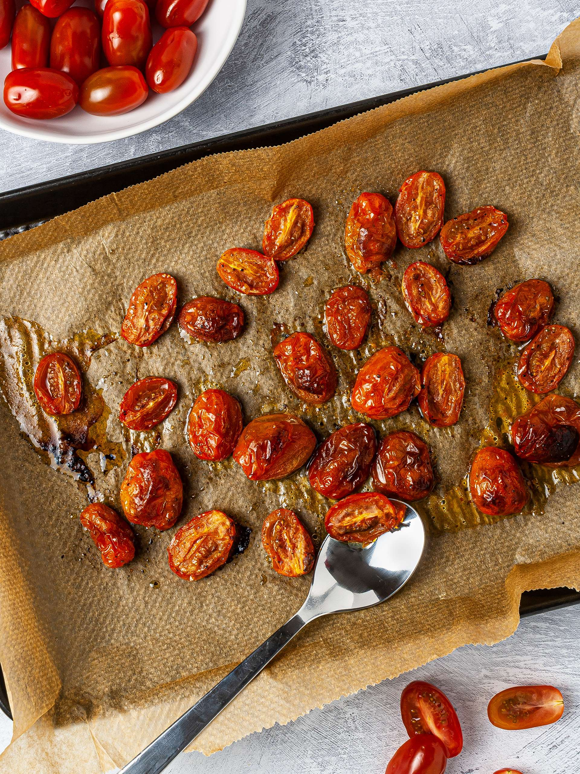 Whole and halved cherry tomatoes roasted with olive oil over a baking tray