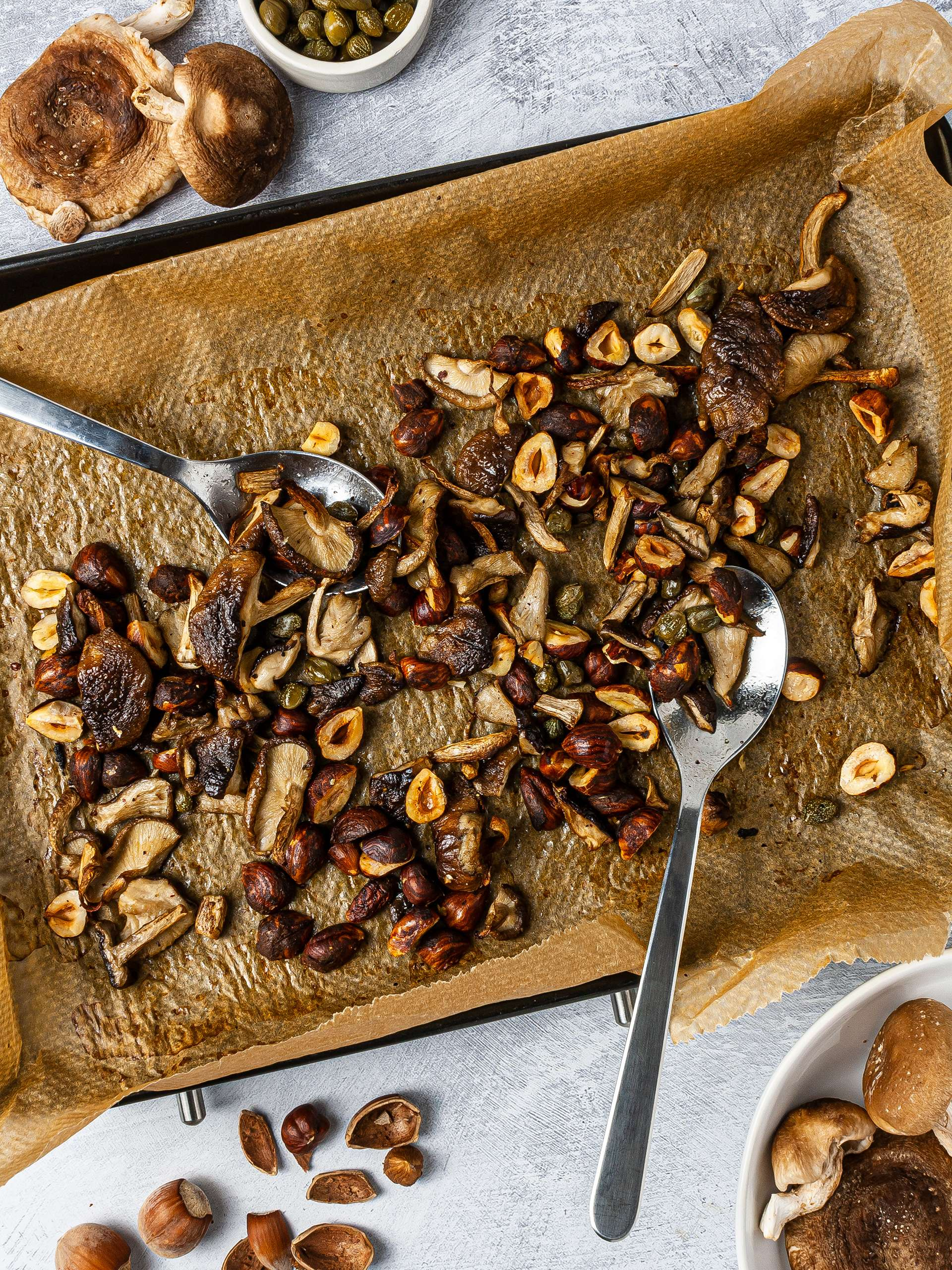 Roasted shiitake mushrooms with hazelnuts and capes over a baking tray