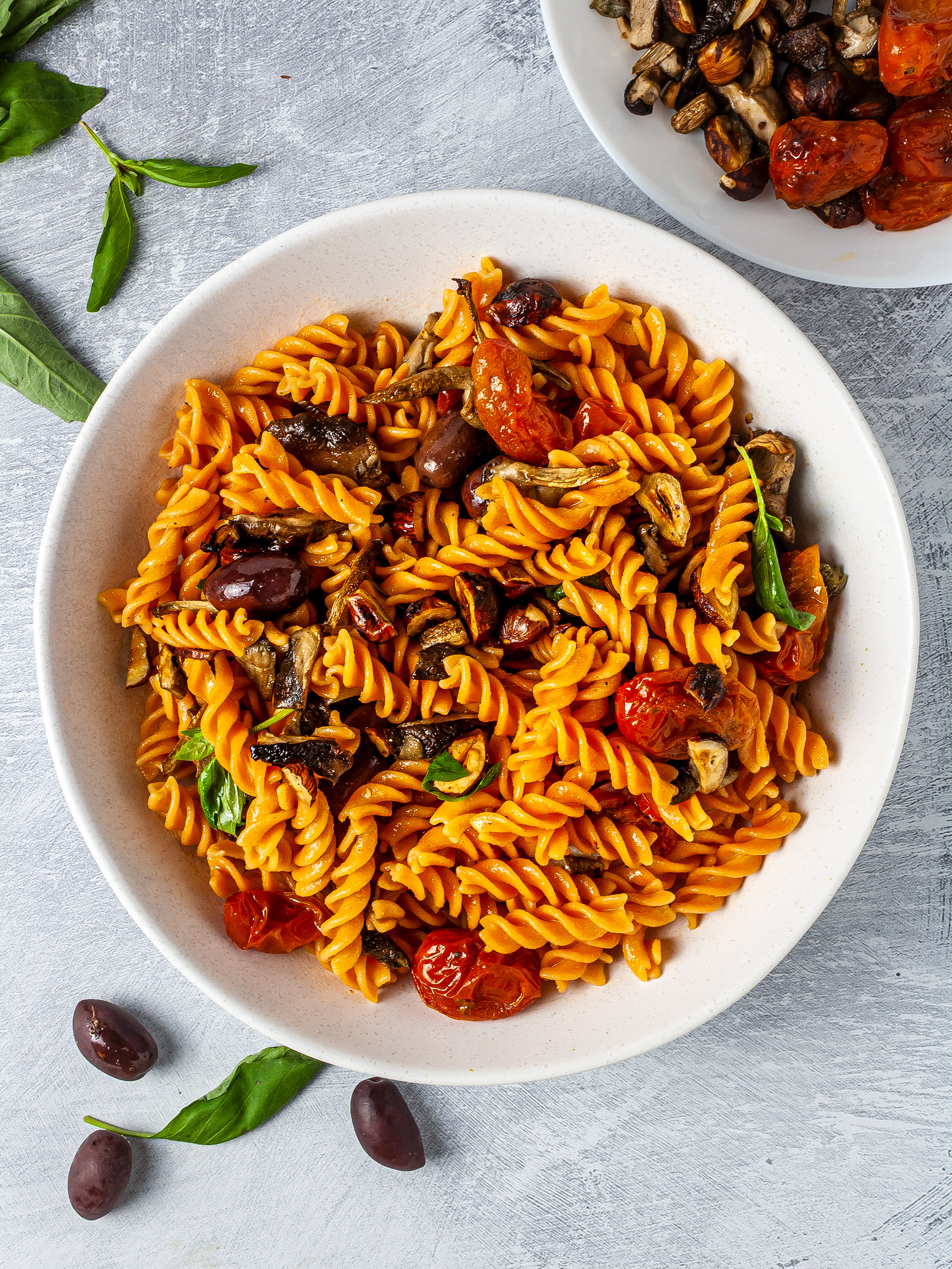 Bowl of pasta salad with fresh basil, olives, roasted cherry tomatoes,