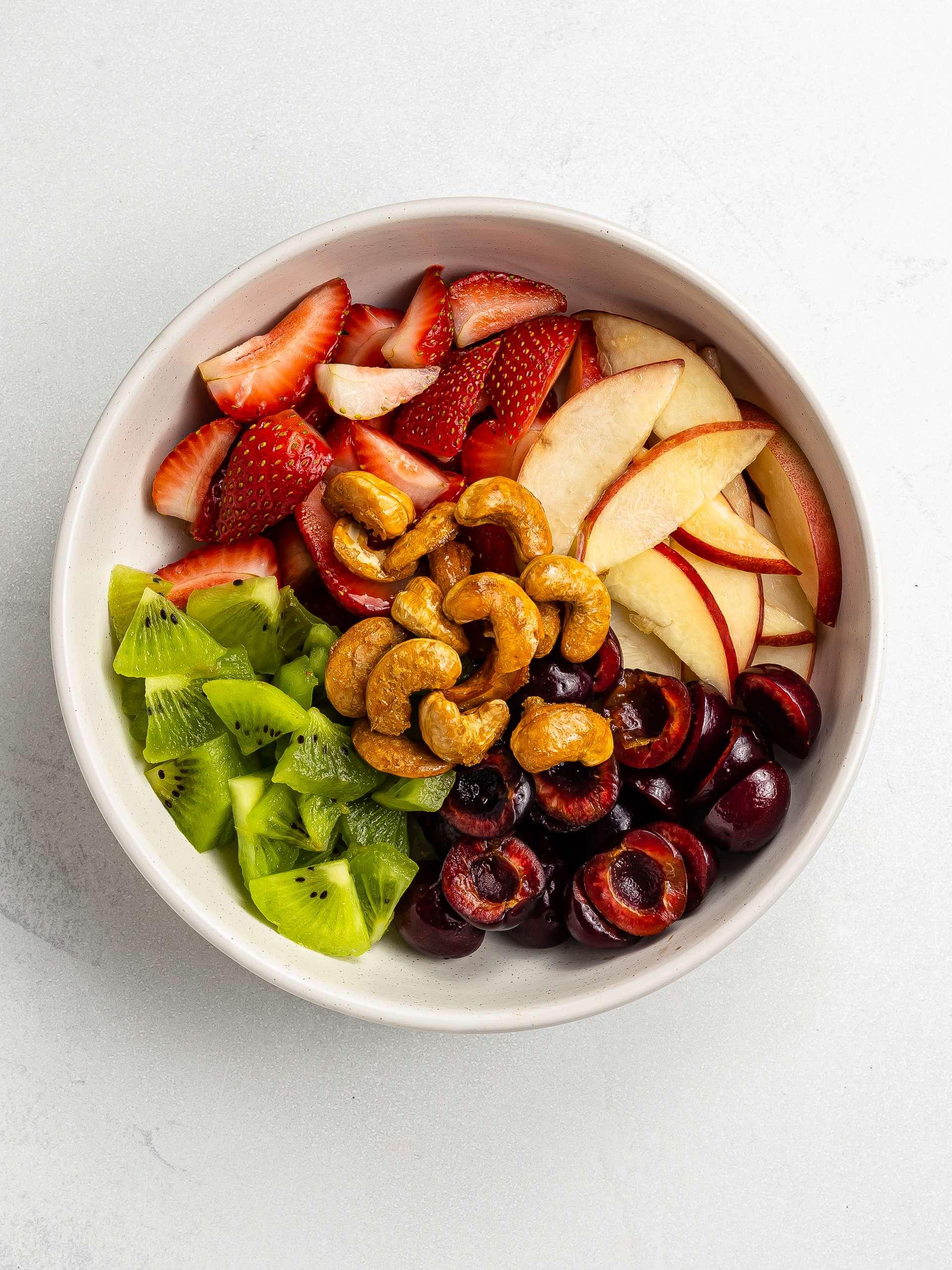 summer fruit salad bowl with caramelised cashews