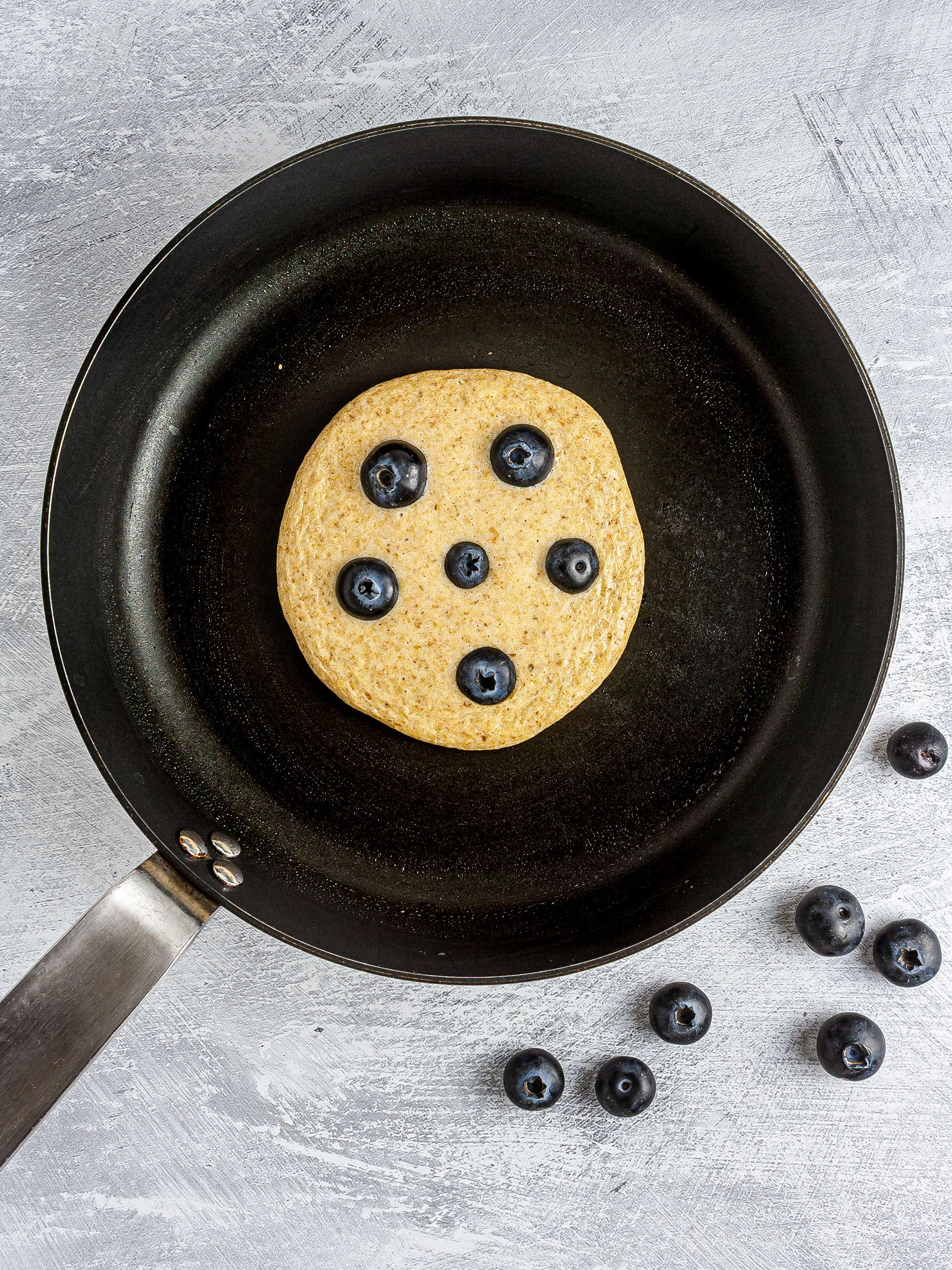 Pancake with blueberries cooking in a pan