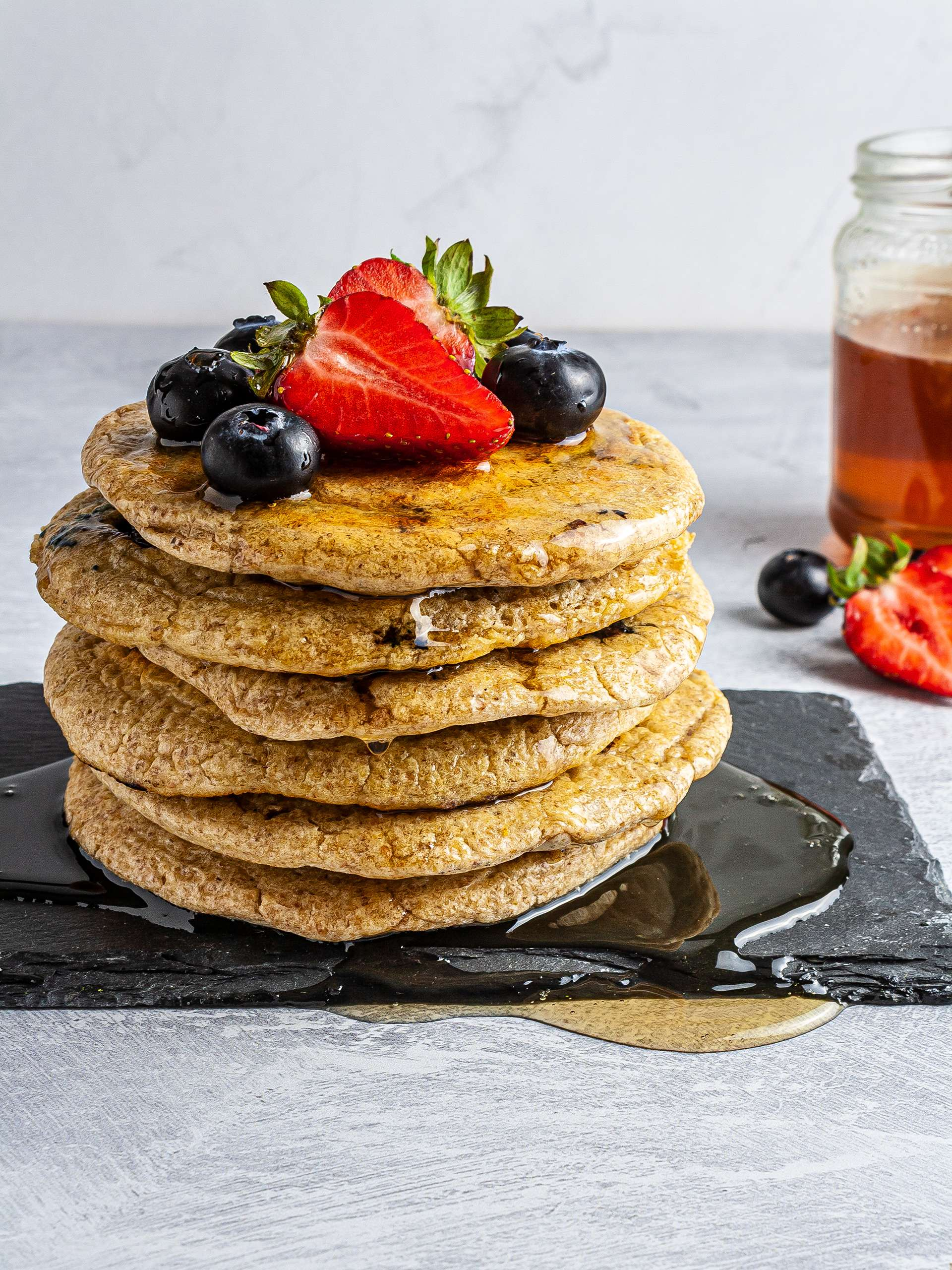 Stacked oatmeal pancakes with blueberries and strawberries
