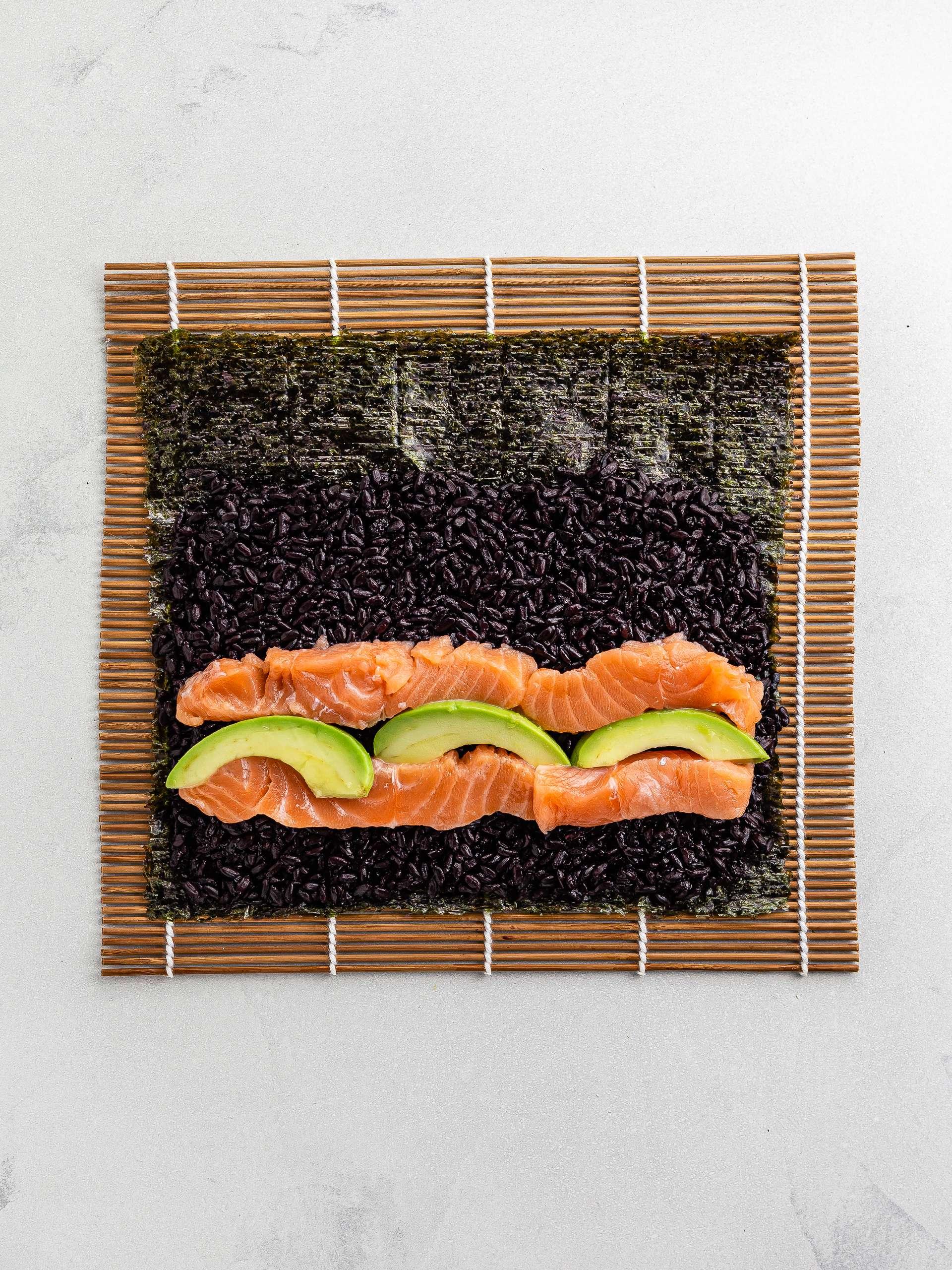 salmon avocado black rice sushi on a mat