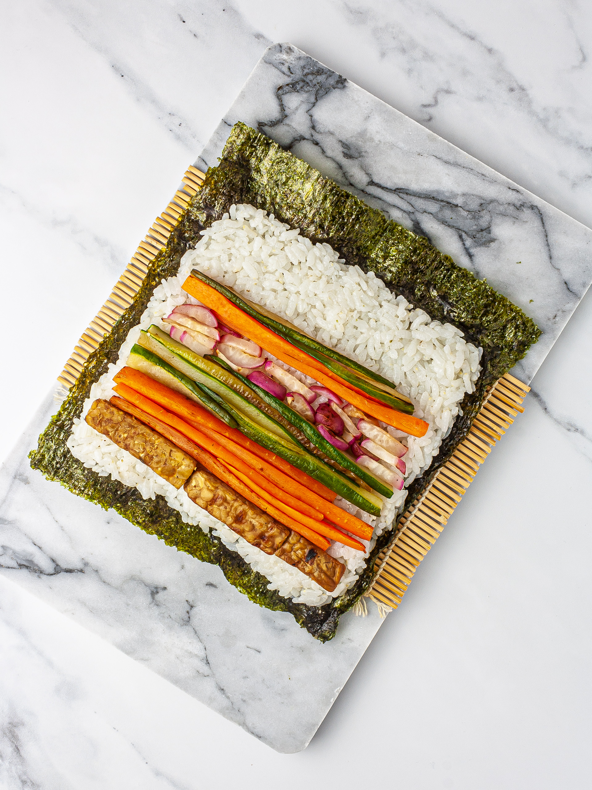 Nori sheet with sushi rice, vegetables, and tempeh on a sushi mat.