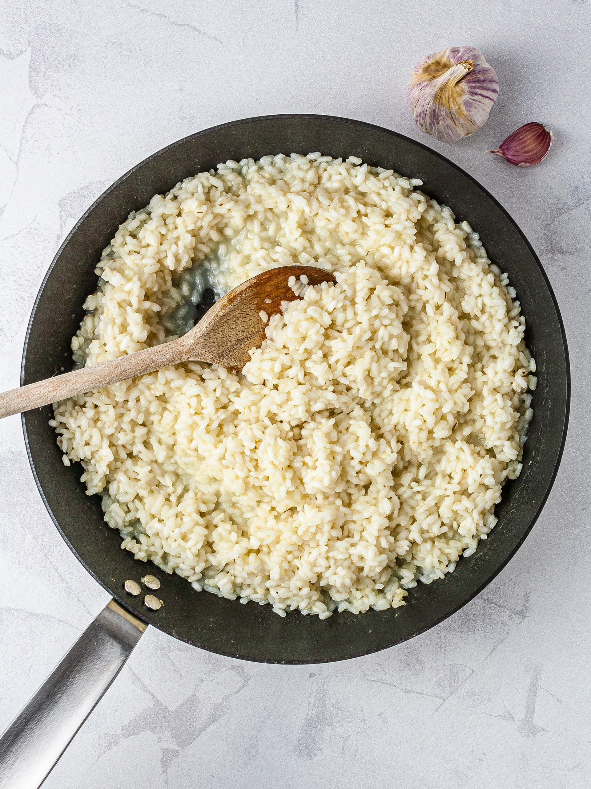 Arborio risotto rice cooked in pan with oil, garlic, and fish stock.