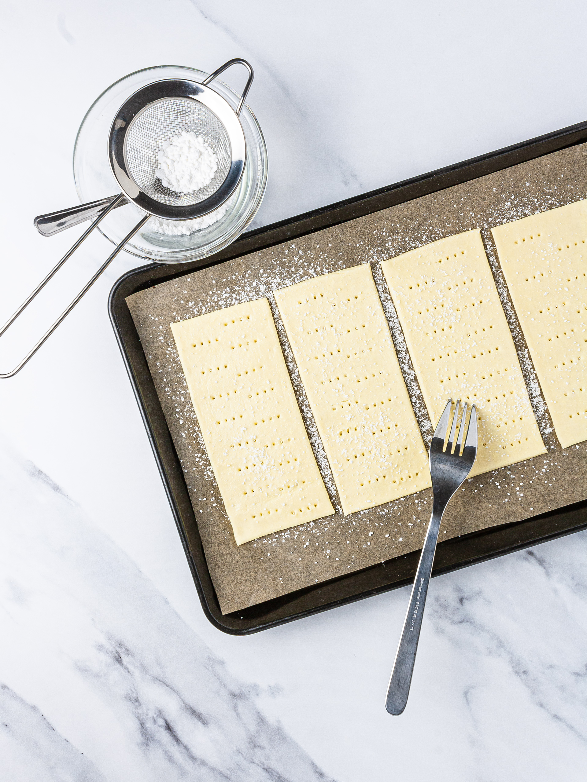 puff pastry sheet in a baking tray poked with a fork