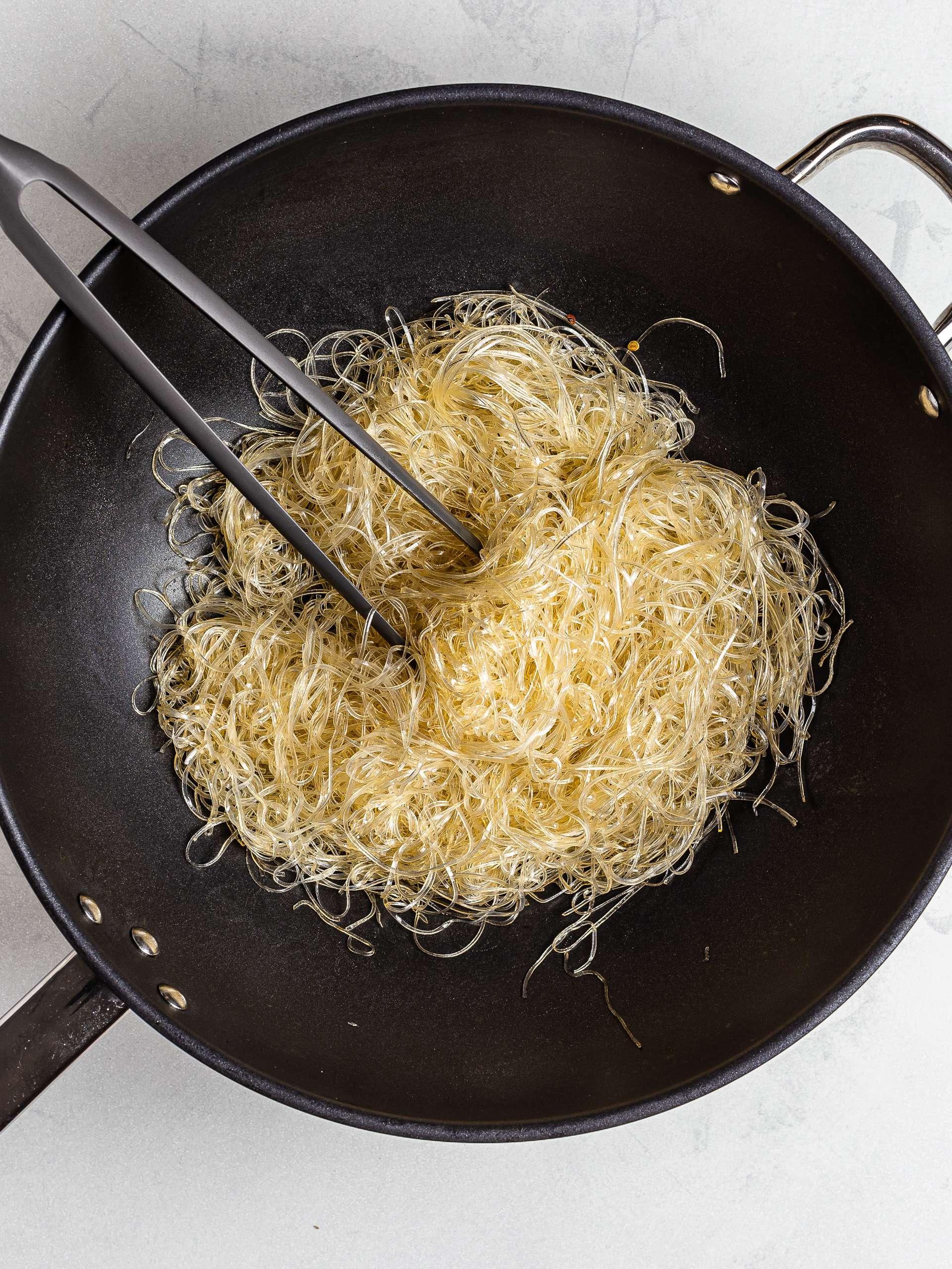 Glass noodles stir fried in a wok