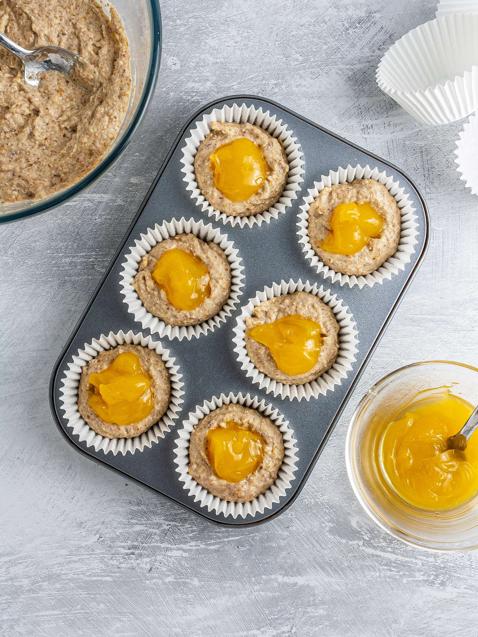 Muffin batter in cases with lemon curd