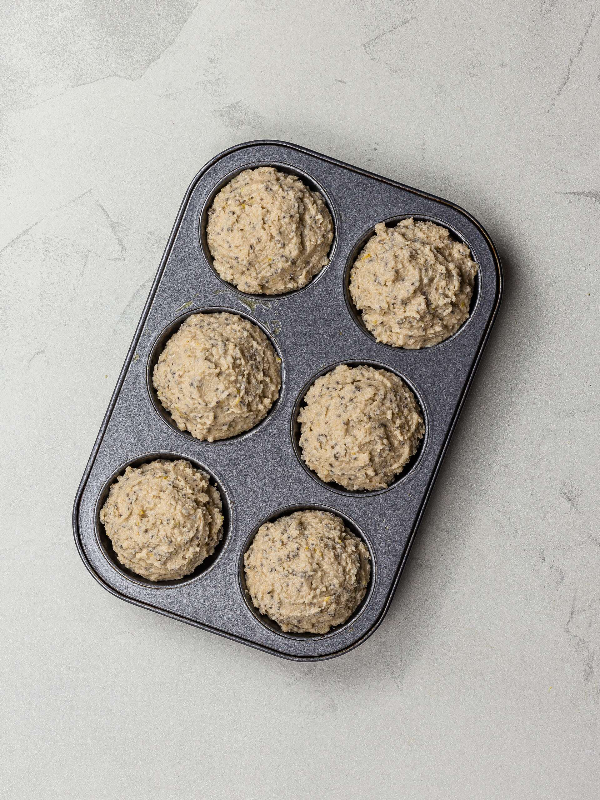 lemon chia seed muffin batter in a muffin tin