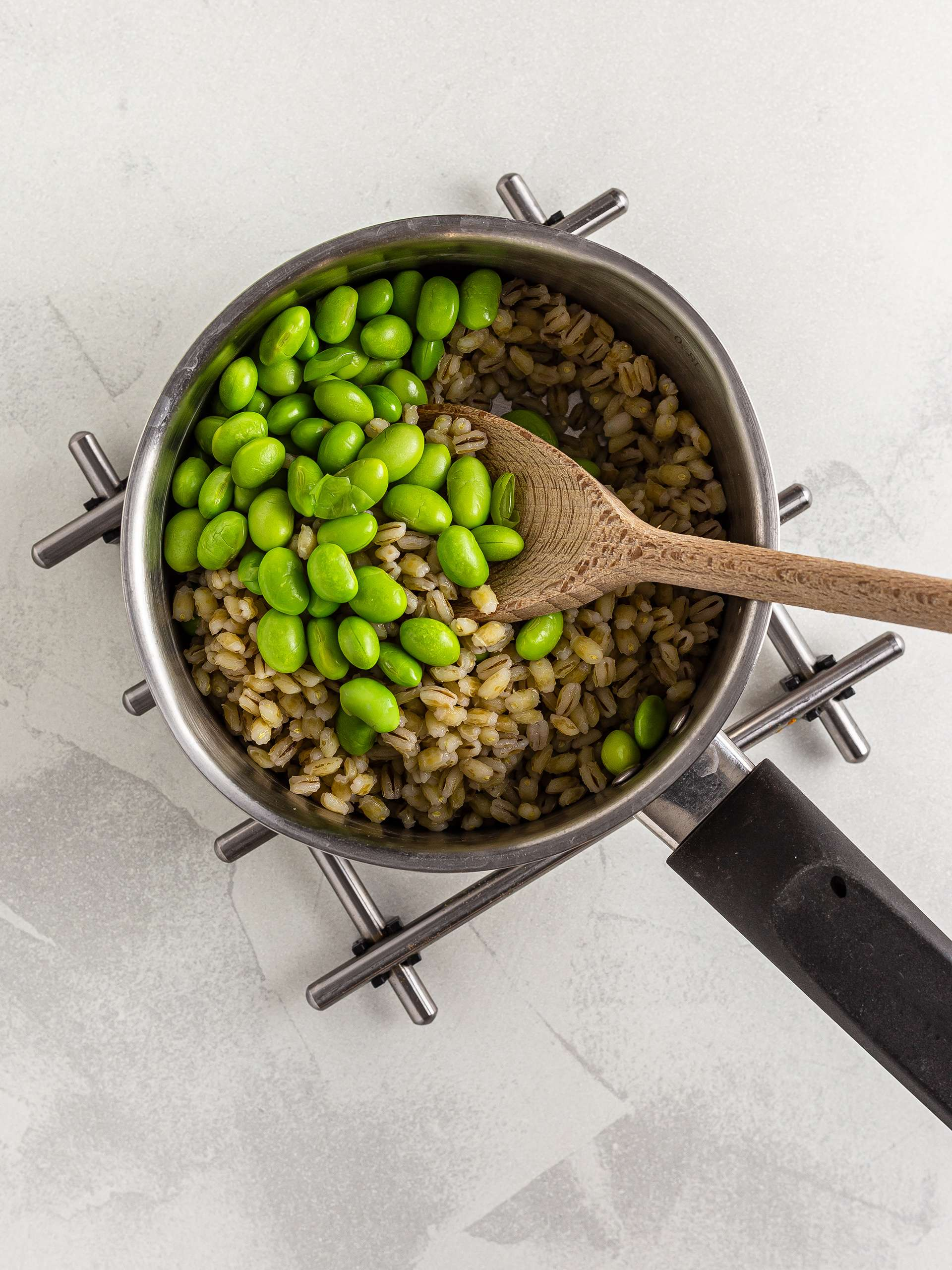 Cooked edamame beans with barley in a pot