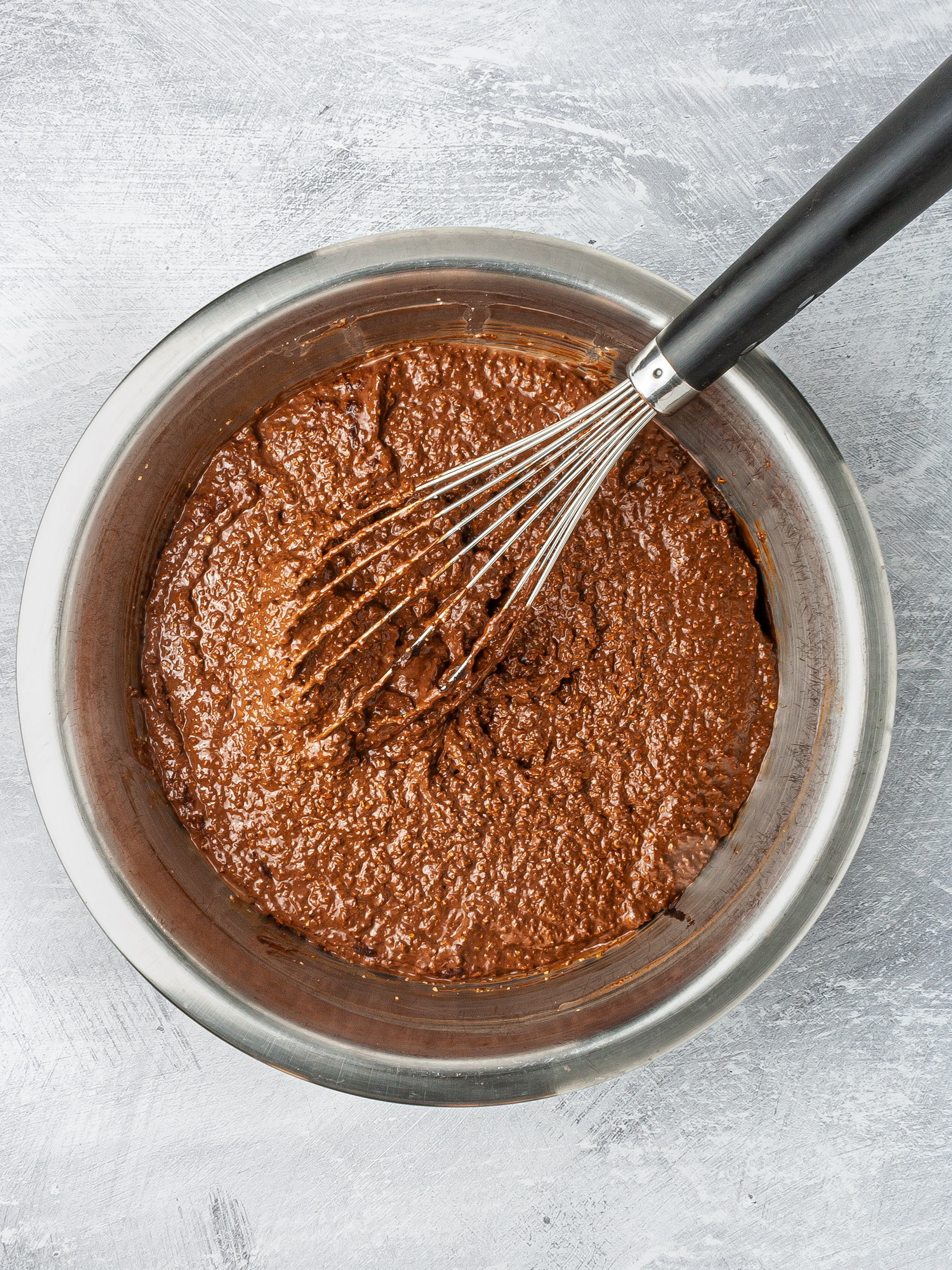 Chocolate lavender cake batter in a bowl with whisker.
