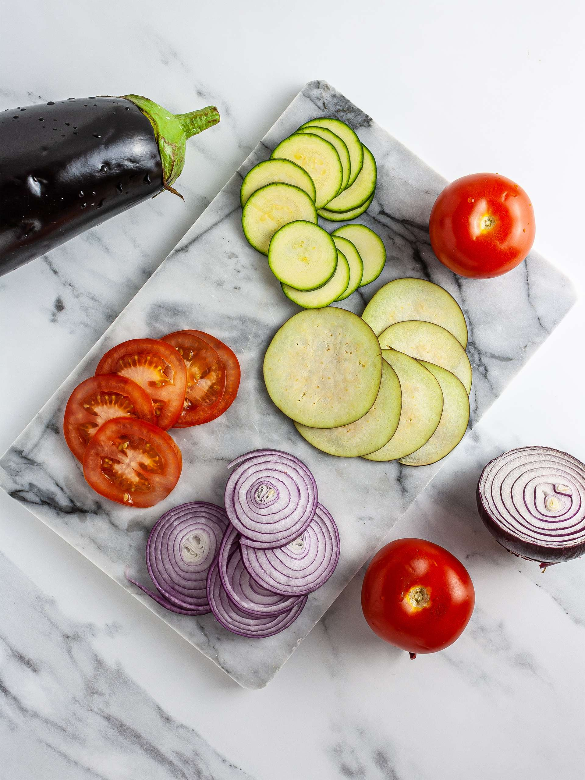 Sliced eggplants, zucchini, onions, and tomatoes